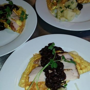 Cuban omelettes stuffed with cheese and yellow rice, topped with sliced pork brisket, black beans and yucca root