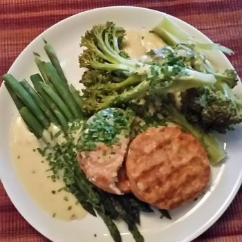 Salmon patties on asparagus and broccoli with a chive hollandaise