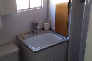 Cozy and cute bathroom with shower in our restored Silver Streak trailer - Casa de los Desperados