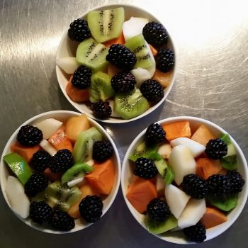 breakfast fruit bowl persimmons pears black berries melon and kiwi
